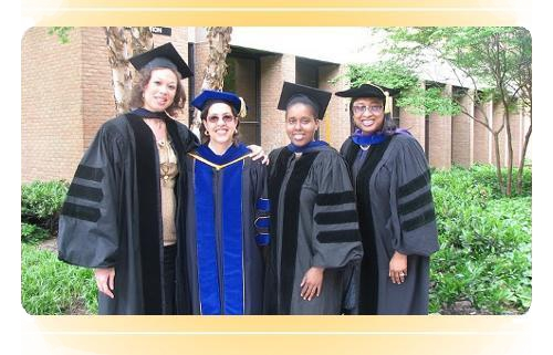 Dean and Associate Vice Provost standing with doctoral graduates