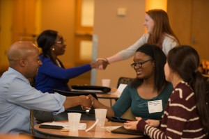 Professionals shake hands with students at UMBC at a career development workshop.