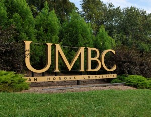 UMBC Sign outside main campus surrounded by bushes.