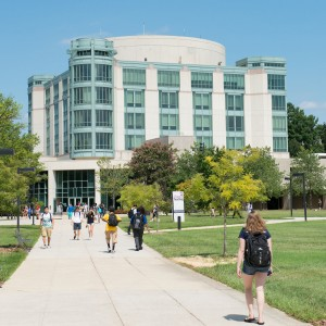 Photo of the campus library with students walking towards the building