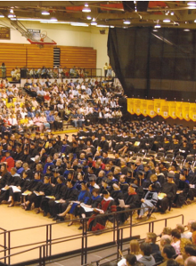 Robed graduating students sit in rows during graduate ceremony